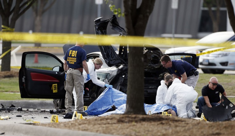 FBI crime scene investigators document the area around two deceased gunmen and their vehicle outside the Curtis Culwell Center in Garland, Texas, Monday, May 4, 2015. Police shot and killed the men after they opened fire on a security officer outside the suburban Dallas venue, which was hosting provocative contest for Prophet Muhammad cartoons Sunday night. (AP Photo/Brandon Wade)