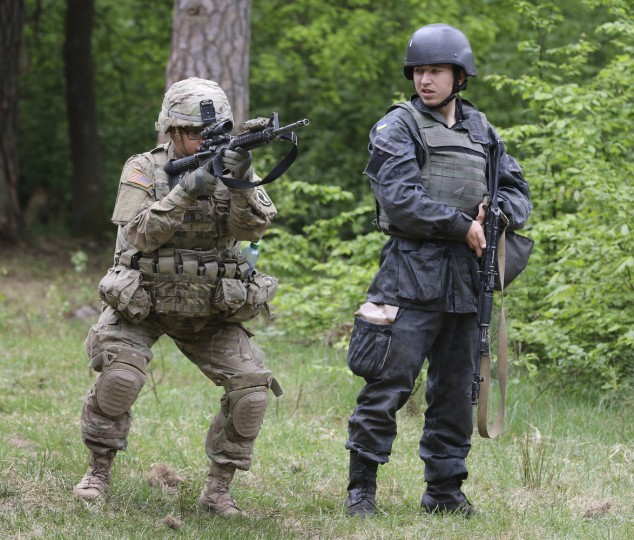 US soldier, left, instructs a Ukrainian soldier during joint training exercises on the military base in the Lviv region, western Ukraine, Thursday, May 14, 2015. Troops from the United States and Ukraine conduct joint training exercises intended to help bolster Ukraine's defense against incursions from Russian-backed separatists. (AP Photo/Evgeny Kraws)
