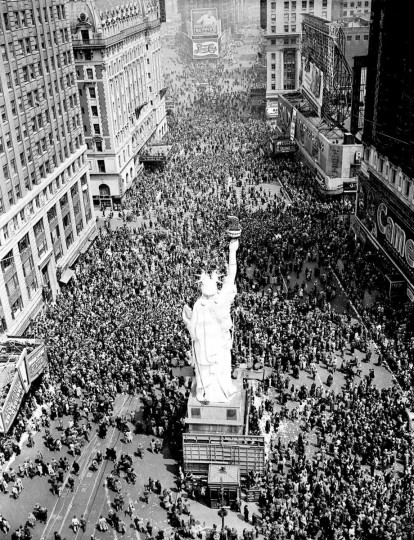 "People crowd Times Square at 42nd Street in New York City on May 8, 1945, as the V-E Day celebration continues into the night. The dim-out and the brownout of the ""Great White Way"" have been replaced once more by the bright lights of victory following World War II. (AP Photo/Matty Zimmerman)"