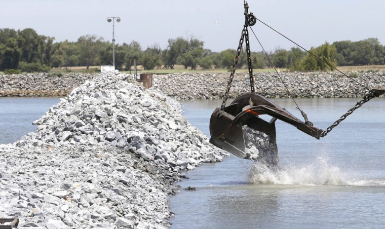A load of rocks are placed during the construction of a temporary emergency barrier to block salt water intrusion into the West False River in the Sacramento-San Joaquin Delta near Oakley, Calif., Friday, May 29, 2015. About 150,000 tons of been used in the construction of the nearly 750-foot-wide barrier, built between Jersey and Bradford Islands by the California Department of Water Resources. The project, which is nearing completion nearly two weeks ahead of schedule, will be removed in mid-November. As less fresh water flows down the rivers, due to California's historic drought, salt water moves farther up the delta which effects the water supply to communities and irrigation water for farmers. (Rich Pedroncelli/AP photo)