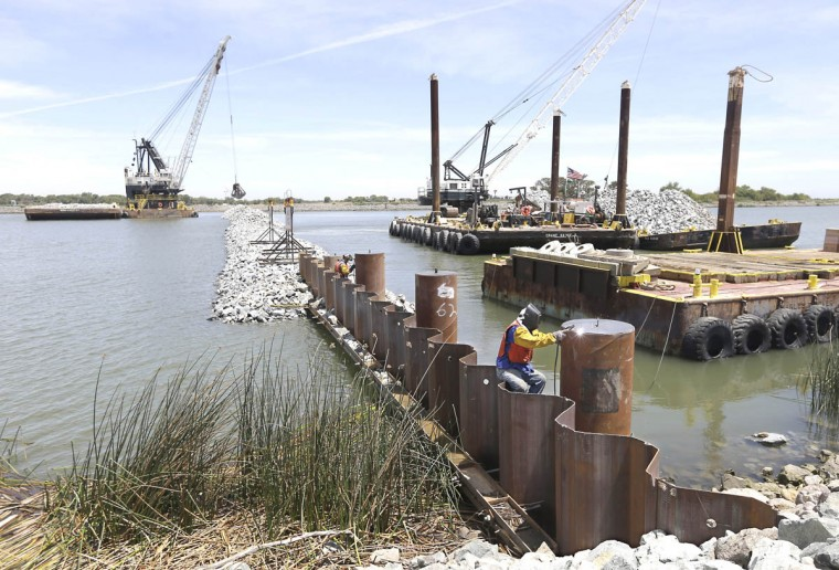A welder works on an abutment support during the construction of a temporary emergency barrier to block salt water intrusion into the West False River in the Sacramento-San Joaquin Delta near Oakley, Calif., Friday, May 29, 2015. About 150,000 tons of been used in the construction of the nearly 750-foot-wide barrier, built between Jersey and Bradford Islands by the California Department of Water Resources. The project, which is nearing completion nearly two weeks ahead of schedule, will be removed in mid-November. As less fresh water flows down the rivers, due to California's historic drought, salt salt water moves farther up the delta which effects the water supply to communities and irrigation water for farmers. (Rich Pedroncelli/AP photo)