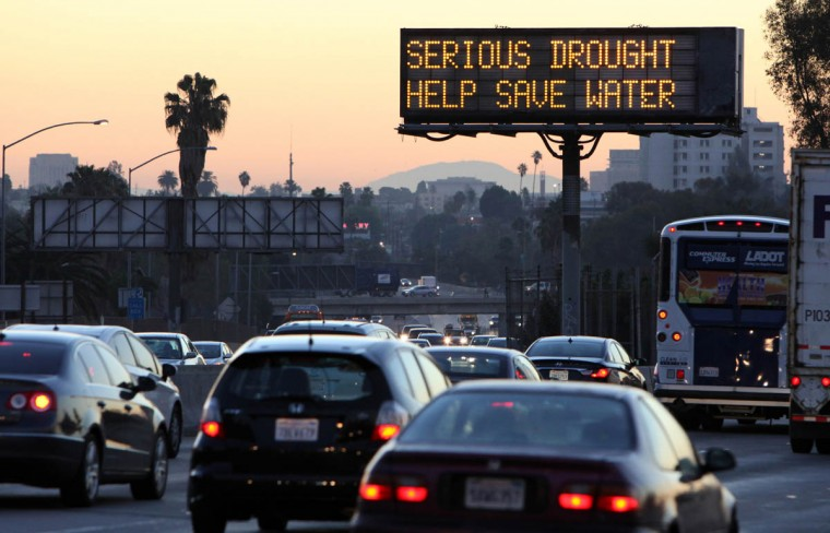 """Morning traffic makes its way toward downtown Los Angeles along the Hollywood Freeway past an electronic sign warning of severe drought. From drought-shaming to eco-boasting, willing or not, celebrities play a role in raising awareness about the debilitating drought in Calif. """"We're all in this together,"""" said actress Wendie Malick. """"Unfortunately, it had to come to this crisis moment to get us all on board."""" (Richard Vogel/AP photo)"""