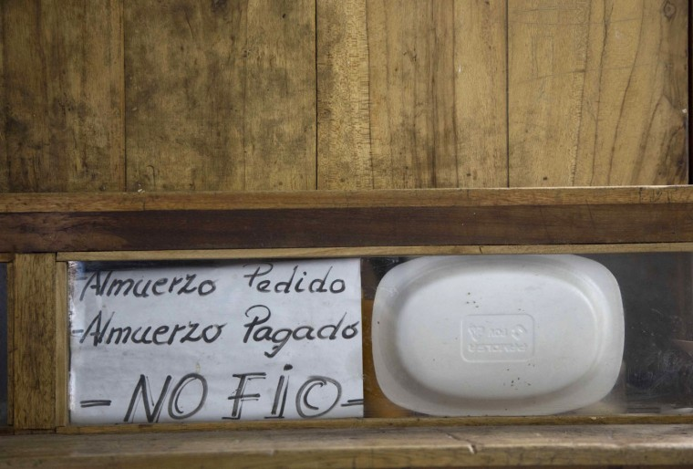 """In this April 14, 2015 photo, a handwritten sign that reads in Spanish """"Ordered lunch. Paid lunch. I don't trust"""" is posted inside a prison cell at the now empty Garcia Moreno Prison, during a guided tour for the public in Quito, Ecuador. The prisoner who used this cell sold food and ran a small general store inside, selling items to his fellow inmates. (AP Photo/Dolores Ochoa)"""