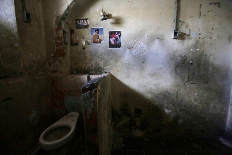 This April 9, 2015 photo shows the bathroom area of a prison cell decorated with pin-up girls and a car at the now empty Garcia Moreno Prison, during a guided tour for the public in Quito, Ecuador. Psychologist Oscar Ortiz, who worked with the inmates behind these walls, says most people believe prison is the worst place, with the worst people. ìBut I have now lived many years and I have concluded that the prison is simply a reflection of our society.î (AP Photo/Dolores Ochoa)