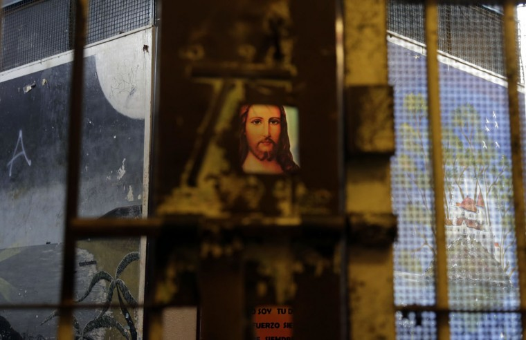 This April 9, 2015 photo shows an image of Jesus through a hole in a gate that separates wings of the now empty Garcia Moreno Prison, during a guided tour for the public in Quito, Ecuador. After prisoners were transferred out in September, guides began giving 30 minute tours through the facility where tourists can get a first hand look at the cells where they slept, and the common areas. (AP Photo/Dolores Ochoa)