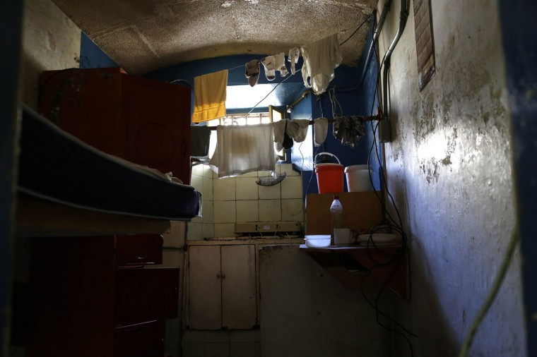 This April 9, 2015 photo shows the inside of a jail cell with personal items left behind by inmates who were transferred away from the now empty Garcia Moreno Prison, during a guided tour for the public in Quito, Ecuador. This cell with two beds was designed to hold just two prisoners, but up to eight people used the room at one time. It measures about eight square meters (86 square feet). (AP Photo/Dolores Ochoa)
