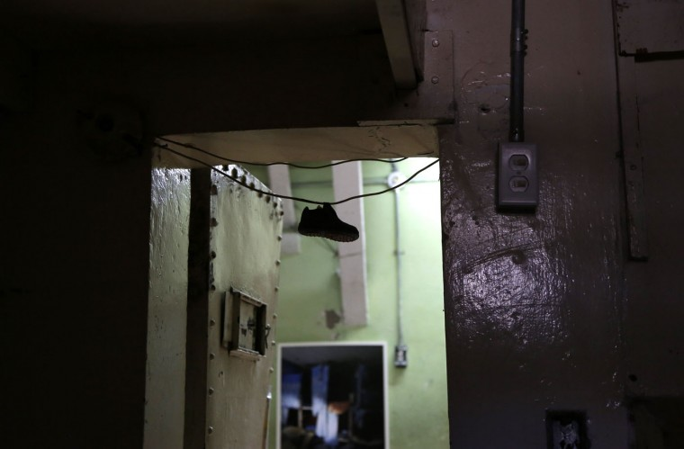 In this April 9, 2015 photo, a child's shoe hangs in the doorway of a cell at the now empty Garcia Moreno Prison, during a guided tour for the public in Quito, Ecuador. Tour guides tell the story of a prisoner who in a jealous rage strangled his wife to death and then hung himself in front of their two children during a family visit years ago. (AP Photo/Dolores Ochoa)