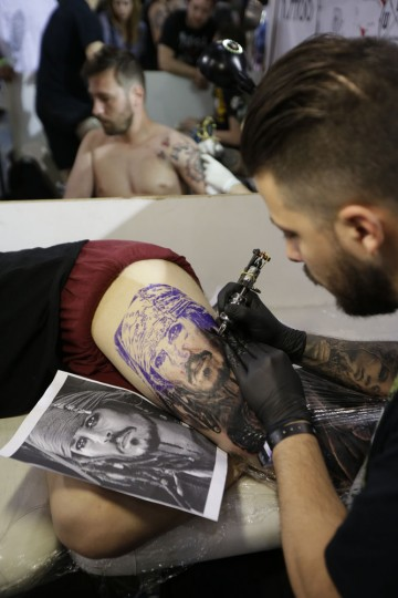 A tattoo artist creates a tattoo of the character of Captain Jack Sparrow from the movie Pirates of the Caribbean on a man's leg during the annual Athens Tattoo Convention in Athens, Sunday, May 17, 2015. About 230 artists from Greece and abroad took part in the three-day event attracted thousands of visitors (AP Photo/Thanassis Stavrakis)