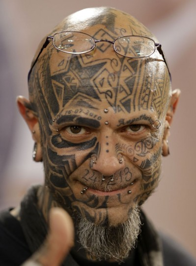 A heavily tattooed man makes a thumb up sign during the annual Athens Tattoo Convention in Athens, Sunday, May 17, 2015. About 230 artists from Greece and abroad took part in the three-day event attracted thousands of visitors. (AP Photo/Thanassis Stavrakis)
