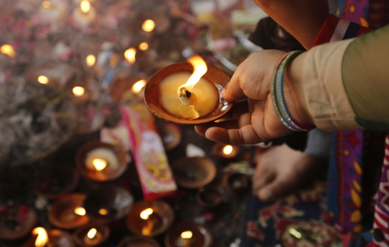 A devotee performs rituals with a lamp at the historic Kheer Bhawani temple in Tul Mul, some 18 miles  northeast of Srinagar, India, on Tuesday. Hundreds of Hindu devotees attended the prayers in the historic Kheer Bhavani Temple during an annual festival dedicated to Hindu Goddess Durga. (Mukhtar Khan/AP)