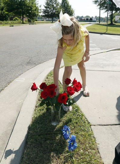 Miller Rose Mozingo, the youngest daughter of Circuit Judge Tony Mozingo, adjusts a bouquet of Mother's Day roses that the family placed near the site where two Hattiesburg, Miss., police were fatally shot the night before, Sunday, May 10, 2015, in Hattiesburg. Three suspects were in custody, including two who are charged with capital murder. (AP Photo/Rogelio V. Solis)