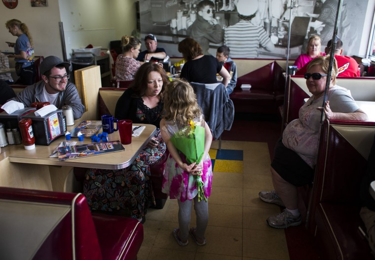Kaydence Brassaw, 5, hides flowers behind her back to give to her grandmother Linda Ratza, 58, for Mother's Day at Starlite Coney Island in Flint, Mich. (Brittany Greeson/The Flint Journal-MLive.com via AP)