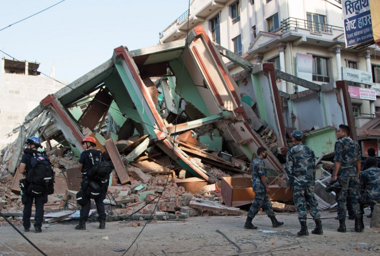 Rescue workers stand beside a building that collapsed in an earthquake in Kathmandu, Nepal, Tuesday, May 12, 2015. A major earthquake has hit Nepal near the Chinese border between the capital of Kathmandu and Mount Everest less than three weeks after the country was devastated by a quake. (AP Photo/Ranup Shrestha)