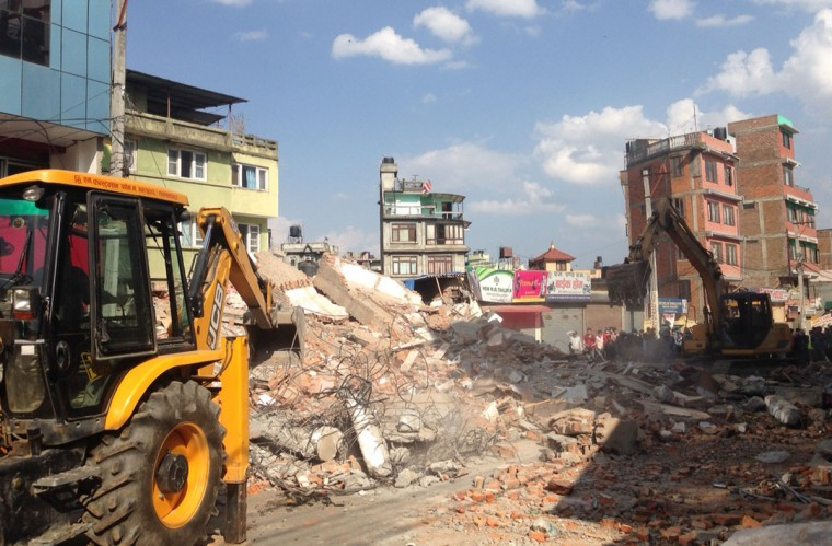 Earthmovers remove debris from a building that collapsed in an earthquake in Kathmandu, Nepal, Tuesday, May 12, 2015. A major earthquake hit Nepal in a remote region near the Chinese border on Tuesday, less than three weeks after the country was ravaged by another deadly quake. (AP Photo/Binaj Gurubacharya)