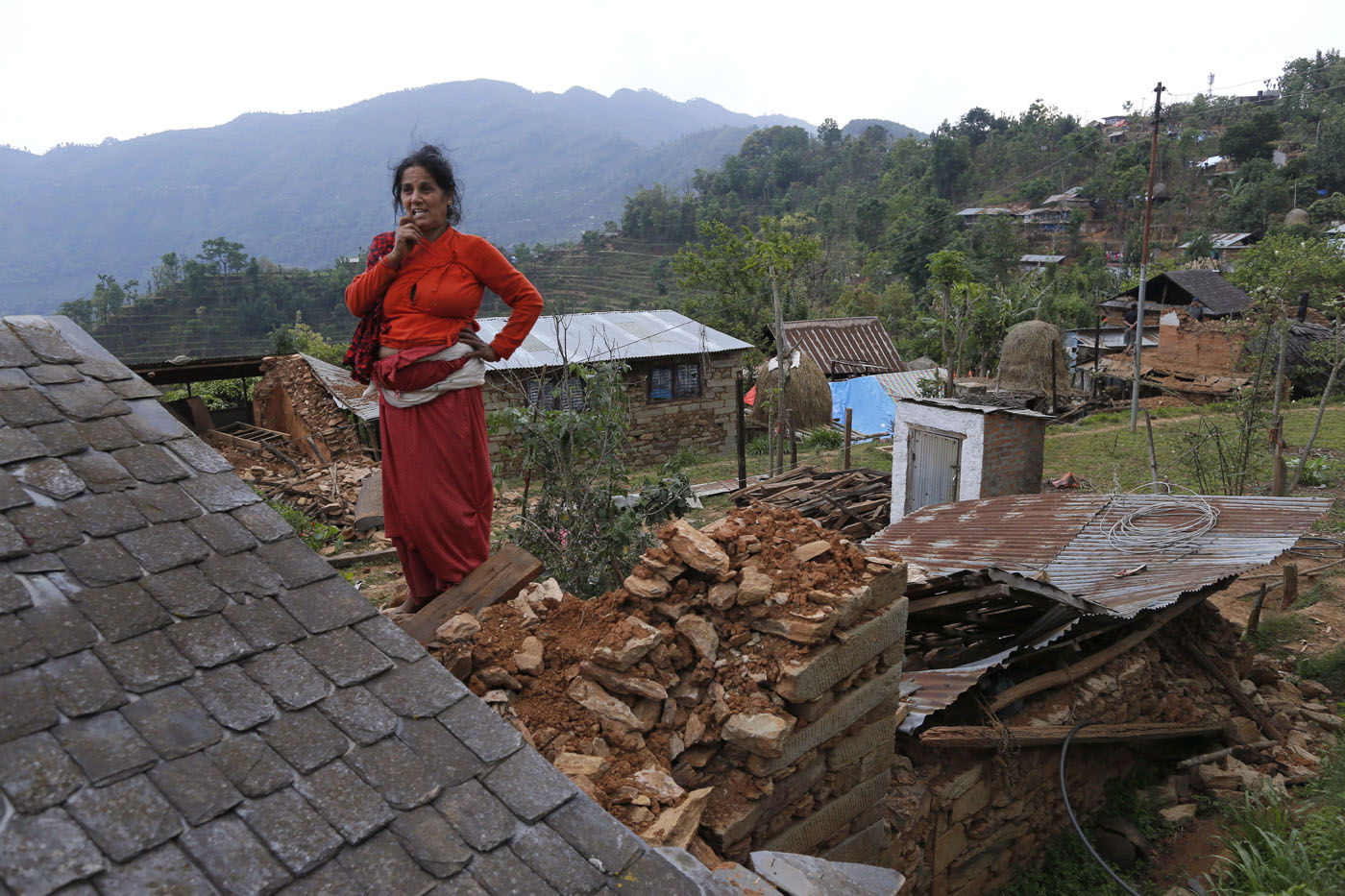 it takes a village surviving the quake in this photo taken on saturday 2 2015 lila khanal gazes over the rubble of her collapsed home in the destroyed village of pokharidanda