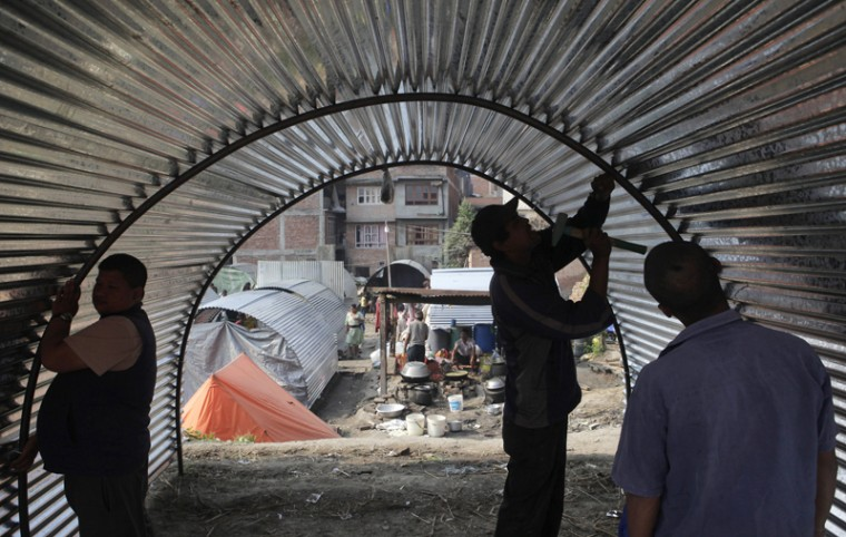 Nepalese people, whose homes were damaged in the April 25 earthquake, construct a temporary shelter made out of galvanized sheet in Bhaktapur, Nepal, on Tuesday. Nepal is facing billions in reconstruction costs with almost 745,600 buildings and homes damaged or destroyed, including at least 87,700 in the capital, according to Nepal's emergency authority. (Niranjan Shrestha/AP)