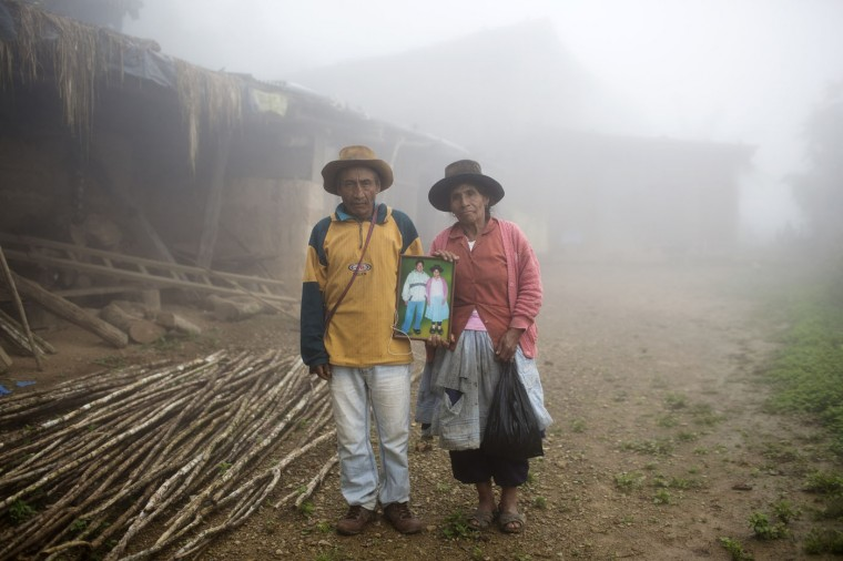 In this March 15, 2015 photo, Julio and Rufina Galvez pose for a picture holding a portrait of their late son Yuri, outside their home, in La Mar province of Ayacucho, Peru. The 25-year-old university student had gotten his fatherís permission to haul coca in a backpack to pay for his agronomy studies, his mother said. Yuri was found face-up on a mountain trail, with bullet wounds to his head, stomach and arm, in a March 2013 cocaine smuggling trip. (AP Photo/Rodrigo Abd)