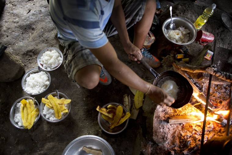 In this March 13, 2015 photo, Donato fries an egg over an open fire to add to his breakfast of rice and plantain, before starting his work day of weeding coca fields, in La Mar, province of Ayacucho, Peru. Roughly one third of the 305 metric tons of cocaine that the U.S. government estimates Peru produces each year travels by foot by way of cocaine backpackers or mochileros, as they are known locally. (AP Photo/Rodrigo Abd)