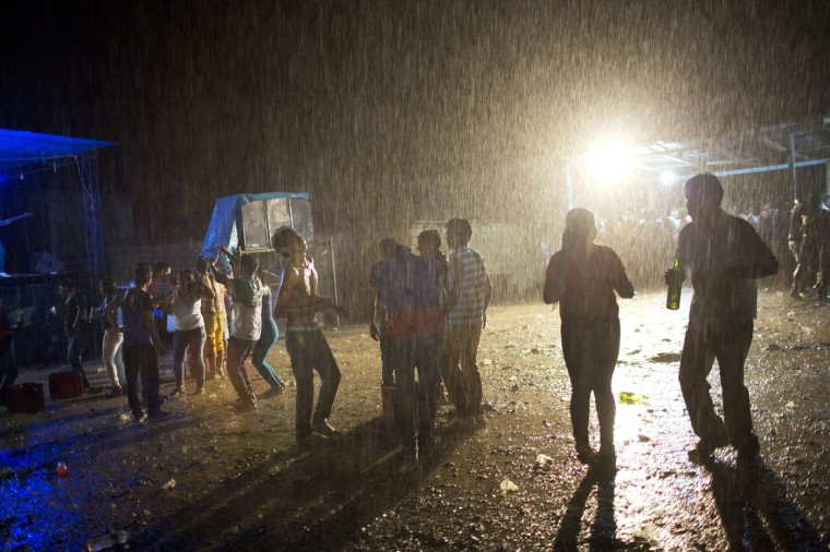 In this March 16, 2015 photo, young people dances under a heavy rain during a concert by huayno singer Ely Corazon, in La Mar, province of Ayacucho, Peru. The average cocaine backpacker, or mochilero, is typically recruited by relatives and friends - often at festivities where liquor flows. They tend not to tell their parents, who nearly always disapprove. (AP Photo/Rodrigo Abd)