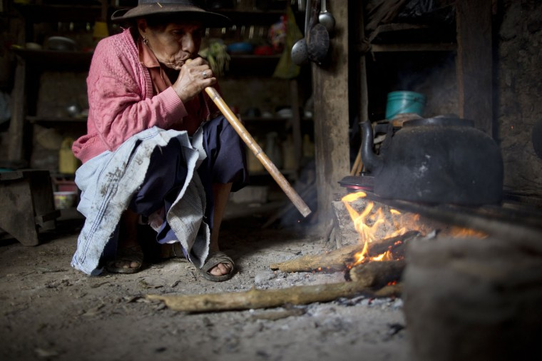 In this March 15, 2015 photo, Rufina Galvez blows into a cane reed to stoke a fire while preparing a special chicken broth to mark the second anniversary of her son's death, in La Mar, province of Ayacucho, Peru. He adored her, ferrying her around Ayacucho on his blue motorcycle, buying her groceries, making sure she always had cell phone minutes, she said. Her son, a university student, had gotten his fatherís permission to haul coca to pay for his agronomy studies. In March 2013, her son was found face-up on a mountain trail, with bullet wounds to his head, stomach and arm. (AP Photo/Rodrigo Abd)