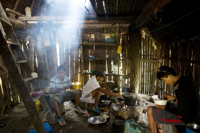 In this March 13, 2015 photo, Donato, from left, Delfin, and Jony, eat breakfast before starting their work day of weeding coca fields, in La Mar, province of Ayacucho, Peru. Peruís cocaine trade is highly decentralized, run by scores of extended families who sell to representatives of foreign cartels. (AP Photo/Rodrigo Abd)