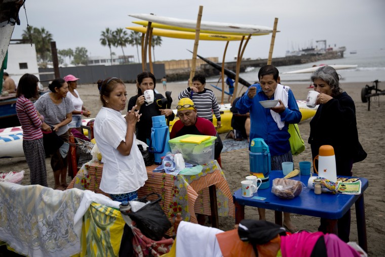 """In this May 15, 2015 photo, swimmers eat breakfast on Fishermen's Beach in the Pacific Ocean in Lima, Peru. The swimmers bought their breakfast from a vendor selling """"health food"""" after their therapeutic swimming session. (AP Photo/Rodrigo Abd)"""