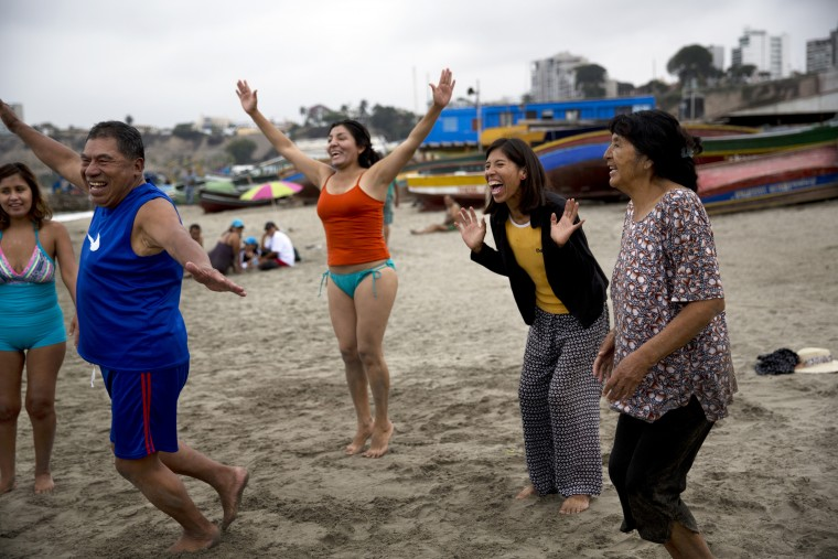 """In this May 8, 2015 photo, people smile during a laugh therapy session on Fishermen's Beach in Lima, Peru. Natural therapy promoter Jose Cusquisiban organizes therapy groups and has his patients jog barefoot on the beach sand. """"Then we make a harmonious circle of prayer, afterward we sing, we practice laugh therapy, we hug and finally we enter the sea and teach those who don't know how to swim,"""" Cusquisiban said. (AP Photo/Rodrigo Abd)"""