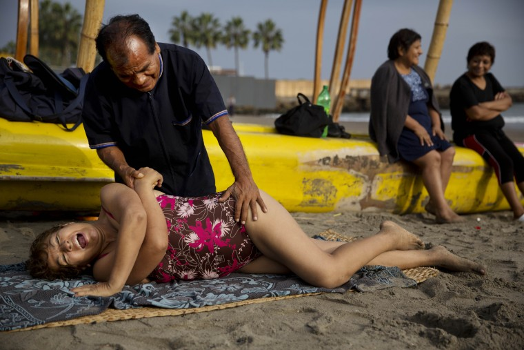 """In this May 15, 2015 photo, chiropractor Felix Retamoso treats Virginia Espinoza's lower back pain on Fishermen's Beach, where she took a therapeutic swim in the Pacific Ocean in Lima, Peru. """"He's not only cheaper, but we're outdoors in direct contact with nature,"""" said the 67-year-old. (AP Photo/Rodrigo Abd)"""