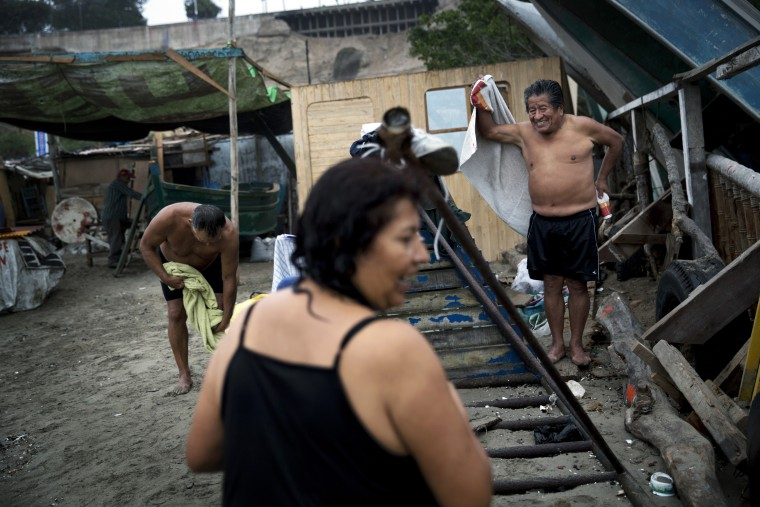 """In this May 13, 2015 photo, people get dressed on Fishermen's Beach after swimming in the Pacific Ocean in Lima, Peru. Under the capital's overcast skies, bathers practice thalassotherapy, which derives from the Greek """"thalasso,"""" for """"sea,"""" and draws on the ocean's healing properties. (AP Photo/Rodrigo Abd)"""