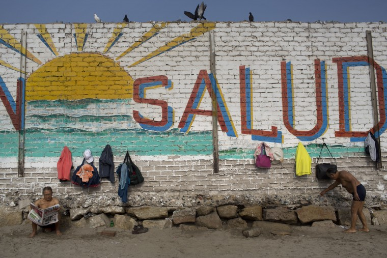 """In this April 25, 2015 photo, a man reads the paper next to a wall decorated with a sun and the Spanish word """"Health"""" on Fishermen's Beach, where bathers come for therapeutic swimming in Lima, Peru. Some hug each other and go in as a group, jumping, laughing and running along the shore. Others bathe silently by themselves in the calm, gray sea water. (AP Photo/Rodrigo Abd)"""