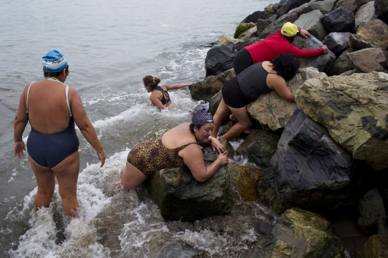 In this April 9, 2015 photo, women embrace rocks before taking a therapeutic swimming in the Pacific Ocean off Fishermen's Beach in Lima, Peru. After meditating, the group lays on rocks as a way to connect with nature, as they do with the sea water, sun and sand. (AP Photo/Rodrigo Abd)