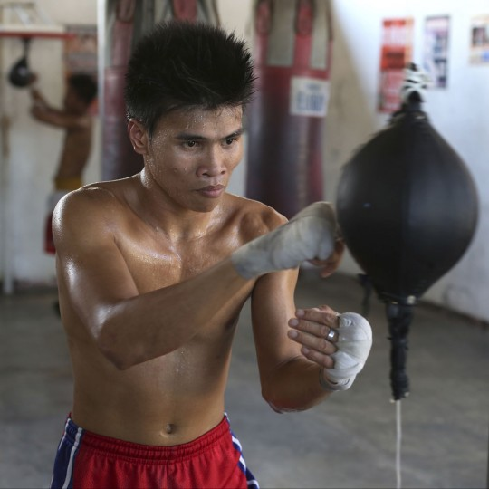 In this April 22, 2015, photo, Filipino boxer Rolly Macaso poses inside a boxing gym in suburban Paranaque, south of Manila, Philippines. Macaso, 21, a former laborer and baker who once scavenged garbage heaps for recyclables, and now hopes boxing leads him to a better life, said. (AP Photo/Aaron Favila)