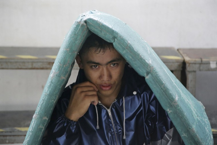 In this April 22, 2015, photo, a Filipino boxer wears a jacket as he sits underneath a mat to help him make weight for his upcoming bout at a boxing gym in suburban Paranaque, south of Manila, Philippines on Wednesday, April 22, 2015. (AP Photo/Aaron Favila)