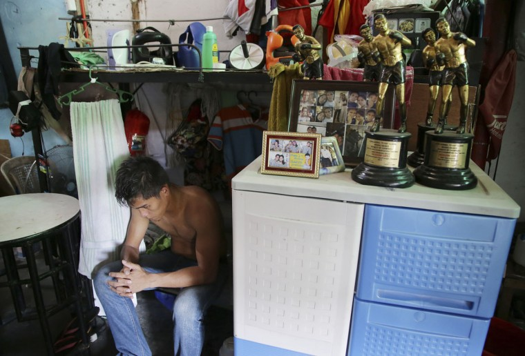 In this April 22, 2015, photo, Filipino boxer Silvestre Lopez sits beside his trophies at a dormitory where they stay during training in suburban Paranaque, south of Manila, Philippines. (AP Photo/Aaron Favila)
