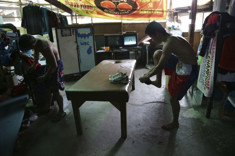In this April 21, 2015, photo, Filipino boxer Meljun Penapin, right, removes his shoes at a dormitory where they stay during training in suburban Paranaque, south of Manila, Philippines. Many young Filipinos aspire to become successful boxers in the country. (AP Photo/Aaron Favila)