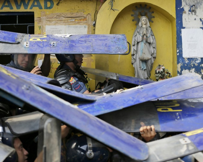 Riot police take cover as residents throw bottles and rocks during the demolition of a squatters' community at suburban Caloocan city, north of Manila, Philippines, on Tuesday. Population growth, poverty and lack of economic opportunities in rural areas have driven millions of Filipinos to urban areas, many settling in squatters' colonies that dot the sprawling metropolitan area in and around Manila. Most of the land they occupy is privately owned, and clearing the dwellings often result in violence. According to residents, the area is home to approximately 500 families, with some having lived there for 50 years. (Bullit Marquez/AP)