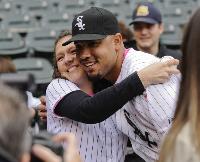 Jody Huffmaster, left, a mother and cancer survivor who threw out a ceremonial first pitch, poses with Chicago White Sox first baseman Jose Abreu before a Mother's Day baseball game against the Cincinnati Reds in Chicago on Sunday, May 10, 2015. (AP Photo/Matt Marton)