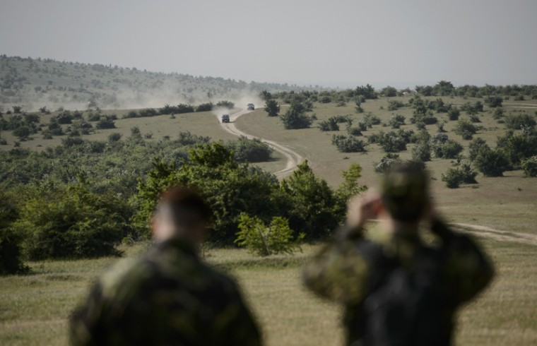 Two armored vehicles speed through a dusty road as two Romanian servicemen watch during a joint military exercise with NATO Allies from Romania and Bulgaria, in Babadag Training Area, in Babadag, south-eastern Romania, on Tuesday. (Andreea Alexandru/Mediafax via AP)