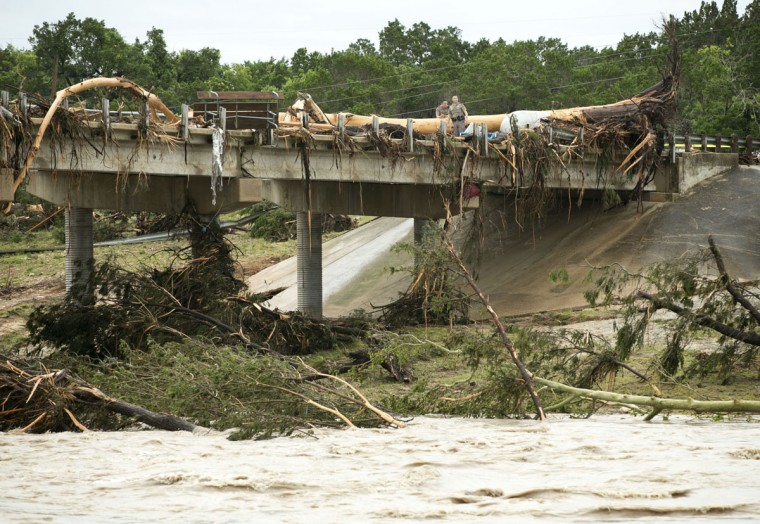 A large tree rests on the Hwy 12 bridge over the Blanco River in Wimberley, Texas, Sunday May 24, 2015. Flooding in Texas and Oklahoma has led to numerous evacuations. (Jay Janner/Austin American-Statesman via AP)