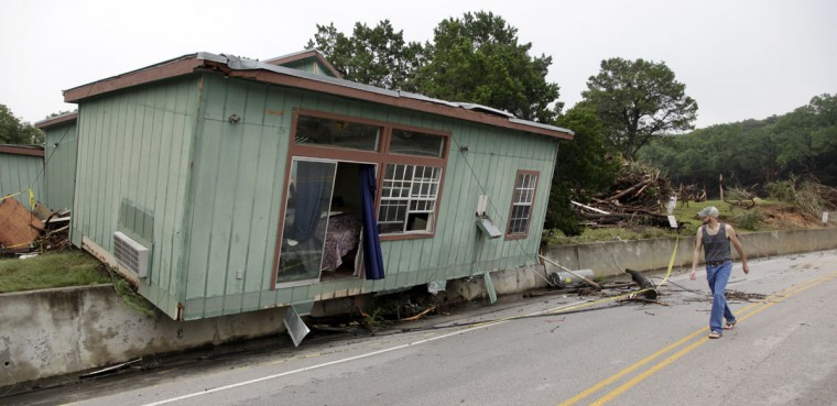 A man walks past a cabin that was torn from its foundation in a flood on the Blanco River days earlier Tuesday, May 26, 2015, in Wimberley, Texas. Recovery teams were searching for as many as 12 members of two families who are missing after the rain-swollen river in Central Texas carried a vacation home off its foundation, slamming it into a bridge downstream. The hunt for the missing picked up after a holiday weekend of terrible storms that dumped record rainfall on the Plains and Midwest, caused major flooding and spawned tornadoes and killed at least eight people in Oklahoma and Texas. (AP Photo/Elaine Thompson)