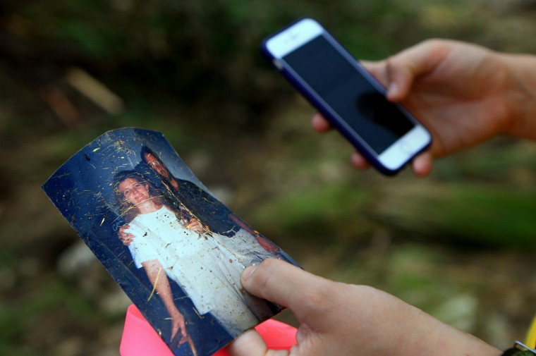 A photo recovered through debris is held by Kayla Massie as she helps search for people who are missing after heavy flooding Wednesday, May 27, 2015, around Umphery Ranch located between Wimberley and San Marcos, Texas. The search went on for about a dozen people, including a group that disappeared after a vacation home was swept down a river and slammed into a bridge. (Gabe Hernandez/Corpus Christi Caller-Times via AP)