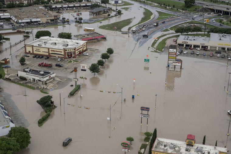 A shopping center located at Texas 80 near I-35 has high water in the parking lots from the Blanco River flooding in San Marcos,Texas, on Sunday, May 24, 2015. (Rodolfo Gonzalez/Austin American-Statesman via AP)
