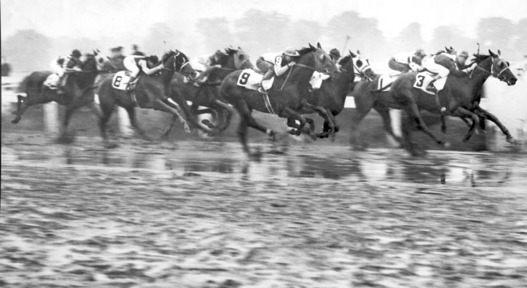 Horses head down the stretch in 1938 during 48th Preakness Stakes, the wettest on record at the time. (Baltimore Sun file photo)