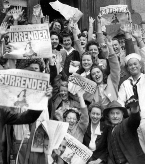 A happy crowd in front of the B&O Building waves copies of the Evening Sun extra announcing the big news. (Baltimore Sun archives)