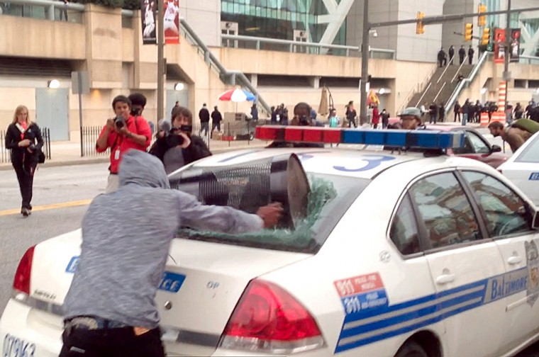 A protestor smashes the back window of a Baltimore police car with a trash can. (Colin Campbell/Baltimore Sun)