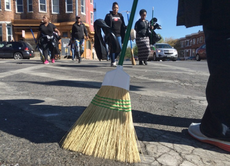 Local residents walk across North Avenue at Fulton Avenue cleaning up the mess from a night of unrest throughout the city. (Karl Merton Ferron/Baltimore Sun)