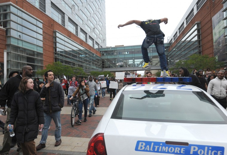 A protester jumps on a Baltimore City police car during protests on Saturday, March 25. (Kim Hairston/Baltimore Sun)