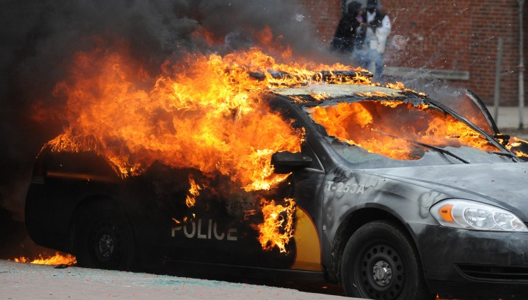 A Maryland Transit Authority patrol car burns at North Ave. and Pennsylvania during Monday's riots. (Jerry Jackson/Baltimore Sun)