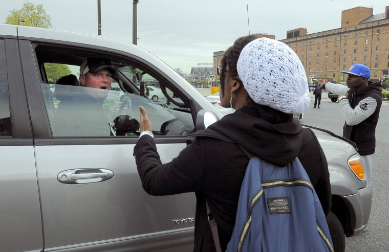 A protester confronts a motorist trying to get to the ball game at Oriole Park during Saturday's Freddie Gray protest. (Jerry Jackson/Baltimore Sun)