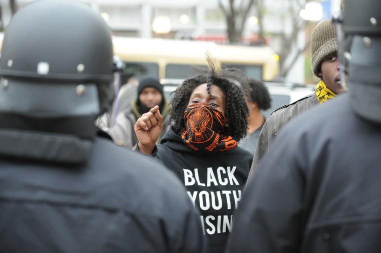 Protester Morgan Lee Malachi of Philadelphia taunts an African-American police officer at Pratt and Howard during Saturday's protest. (Jerry Jackson/Baltimore Sun)